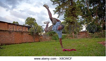 teenage boy showing a breakdance figure on a lawn doing a handstand on one arm, Burundi, Makamba, Makamba - Stock Photo