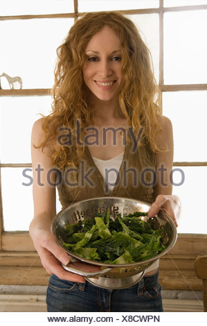 Woman holding bowl of vegetables - Stock Photo