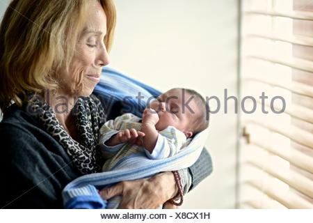 Grandmother holds her first granddaughter,a two-week-old baby girl. - Stock Photo