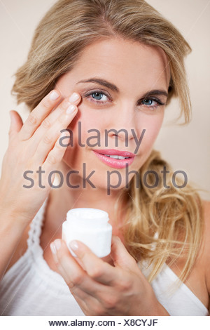 A young blond woman applying moisturizer to her face, close up - Stock Photo