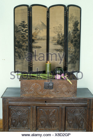 Close-up of antique folding Chinese screen on carved wooden box on carved antique wooden chest - Stock Photo