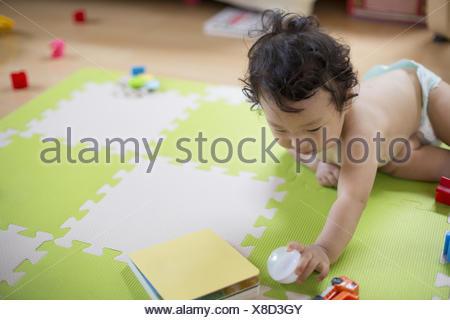Baby boy playing indoors. - Stock Photo