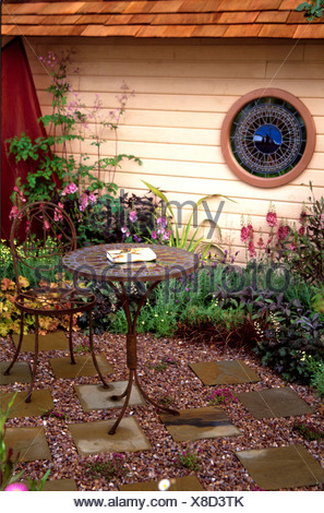 Small gardens at Hampton Court  Patio area paving slabs set in gravel small purple flowers planted in, rusted table mosaic - Stock Photo