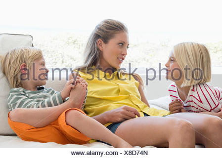 Happy mother and children sitting on couch in living room