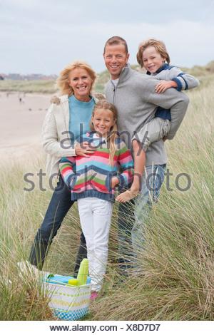 Family Walking Along Winter Beach With Picnic - Stock Photo