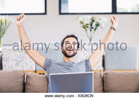 Handsome man rejoicing with laptop on legs - Stock Photo
