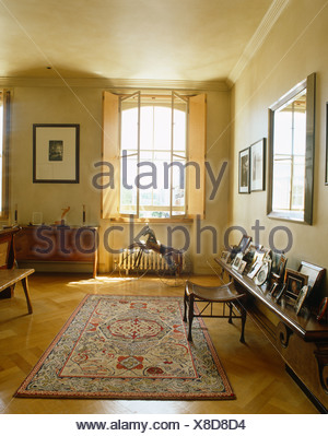 Shutters on window above metal horse in bedroom with patterned rug on parquet floor - Stock Photo