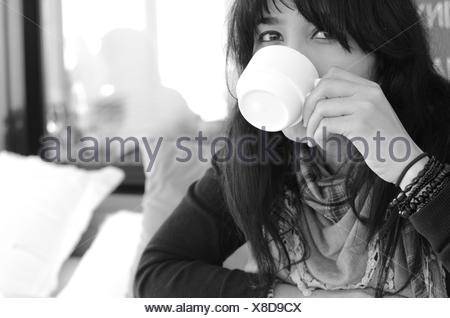 Portrait of woman drinking coffee - Stock Photo