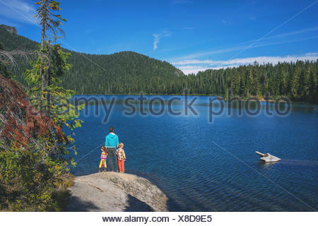 Man with two children standing on a rock by lake - Stock Photo