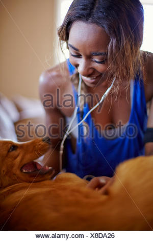 Young woman on a training break, petting dog in sitting room - Stock Photo