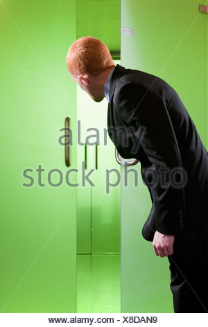 Young Businessman Looking Through Window; Man Looking Through Green Glass  Doors   Stock Photo