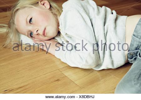 Young girl lying on wooden floor, looking away - Stock Photo