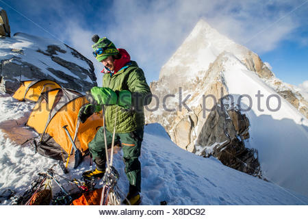 An expedition member double checks his ropes and gear. - Stock Photo