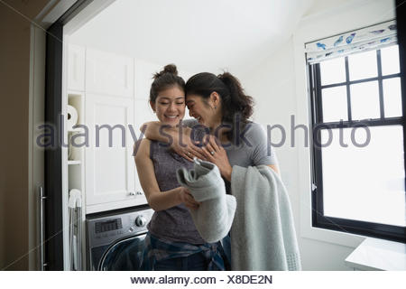 Mother hugging teenage daughter folding laundry - Stock Photo