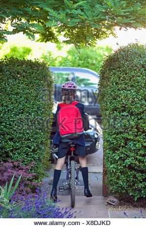Young girl (12-13) going to school on bike - Stock Photo