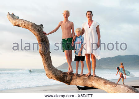 Costa Rica, Santa Teresa, Mother with two sons (10-11, 14-15) on beach - Stock Photo