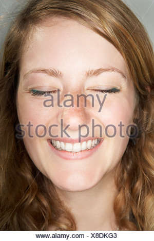 Young female with eyes closed smiling - Stock Photo