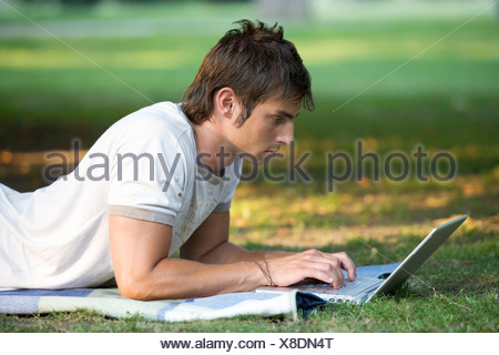 A teenage boy working on a laptop in a park - Stock Photo