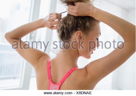Young woman tying hair - Stock Photo