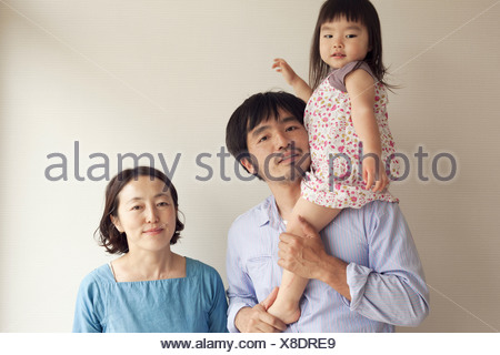 Girl on father's shoulder with mother, portrait - Stock Photo