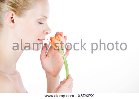 A young woman smelling an orange tulip, side view - Stock Photo