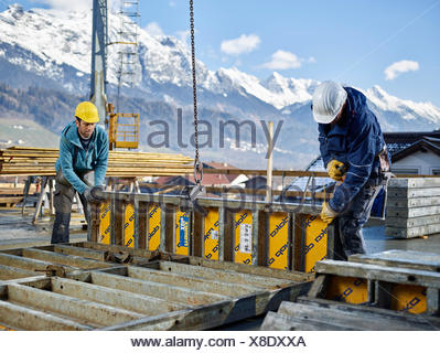 Construction workers lifting shuttering wall with crane, preparing framed formwork, Innsbruck Land, Tyrol, Austria - Stock Photo