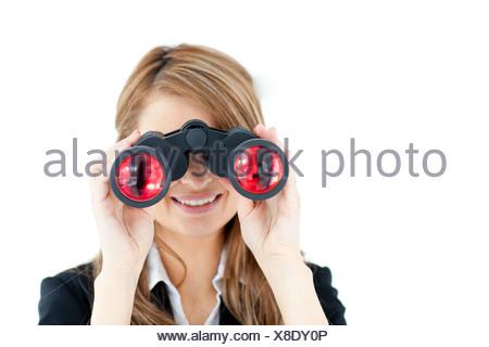 Positive businesswoman looking through binoculars - Stock Photo