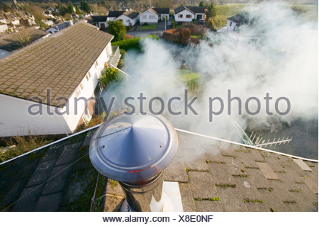 A household chimney emmiting smoke - Stock Photo