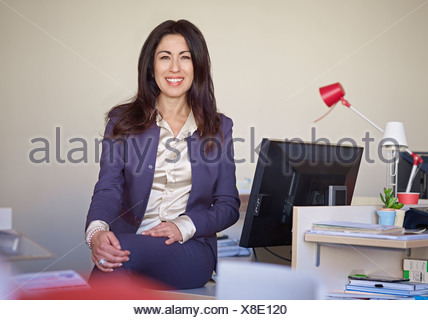Businesswoman wearing suit sitting at desk - Stock Photo