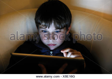 Boy, 8, using an iPad, Ringsheim, Baden-Wuerttemberg - Stock Photo