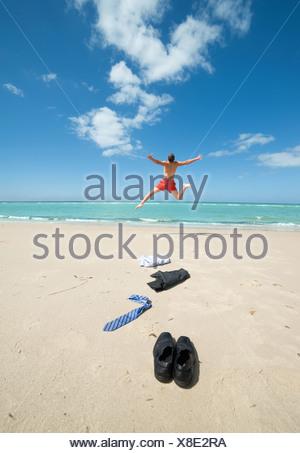 businessman jumping on the beach - Stock Photo