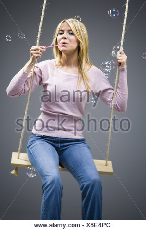 Woman blowing bubbles on swing - Stock Photo
