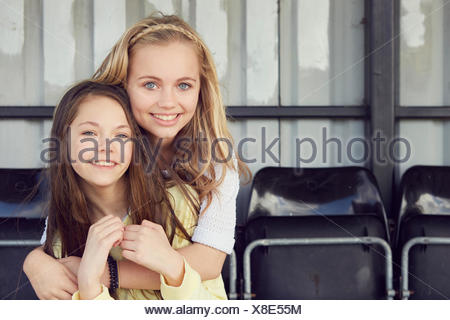 Portrait of two girls hugging in stadium stand - Stock Photo