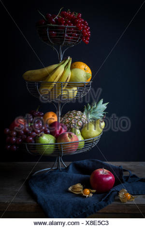 Fresh fruits in metal étagère before dark background - Stock Photo