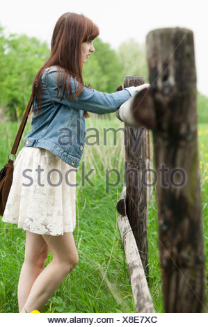 Young woman leaning on wooden fence - Stock Photo
