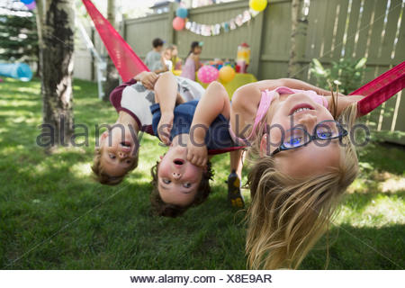 Portrait upside-down kids hammock backyard birthday party - Stock Photo