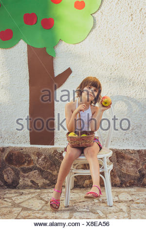 Girl sitting on chair with a basket of apples - Stock Photo