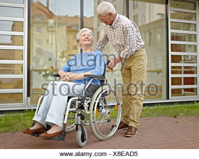 Germany, Cologne, Senior man pushing woman in wheelchair - Stock Photo