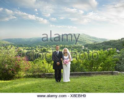 Wedding couple in sunlit garden - Stock Photo