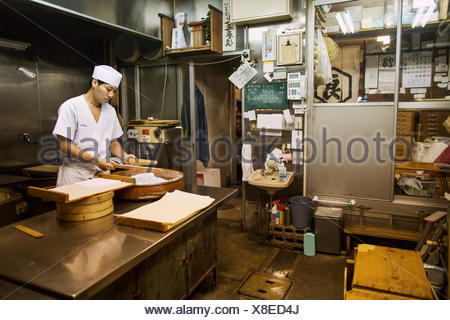 A small artisan producer of wagashi. A man mixing a large bowl of ingredients and pressing the mixed dough into moulds in a commercial kitchen. - Stock Photo