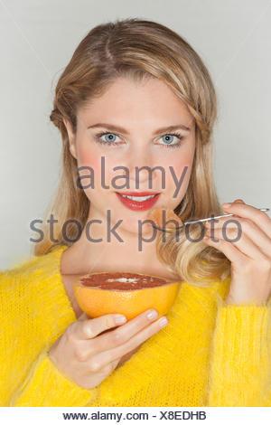 Portrait of a beautiful woman eating grapefruit - Stock Photo