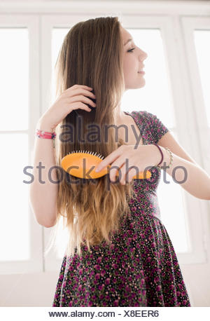 Teenage girl getting hair care with brush - Stock Photo
