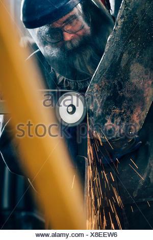 Blacksmith grinding metal on machine in metal workshop - Stock Photo