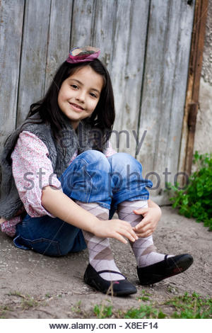 Girl sitting on ground leaning against wooden fence - Stock Photo