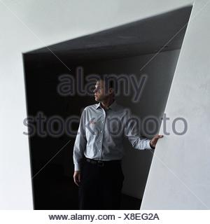 Young Man Looking Away Against Wall - Stock Photo