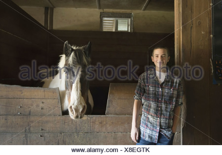A man standing by horsebox in the stables at an animal sanctuary A horse with its head over the gate Saugerties New York USA - Stock Photo