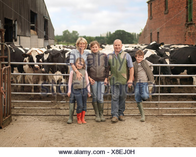 Farmer And Family With Cows - Stock Photo