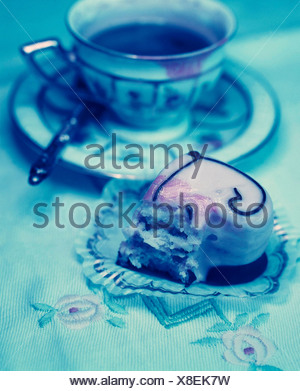 Half-eaten heart-shaped petit four and an old coffee cup - Stock Photo