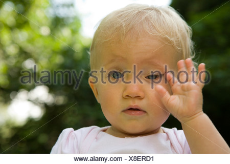 A tired 10 month old baby girl - Stock Photo
