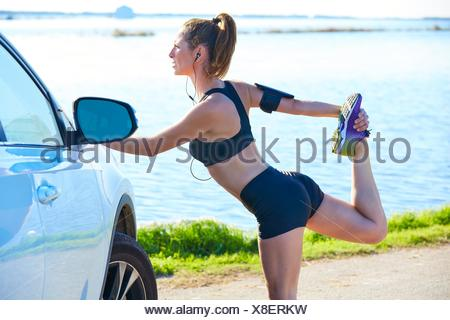 Runner woman stretching on a car in the lake outdoor. - Stock Photo